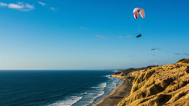 Paragliders soar over the San Diego coastline
