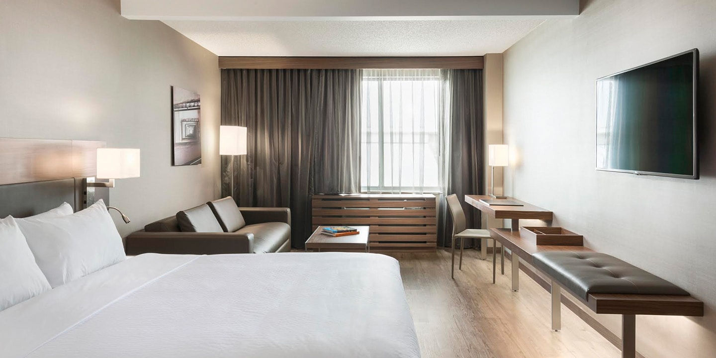 AC Hotels guestroom with bed, sofa and wall-mounted TV