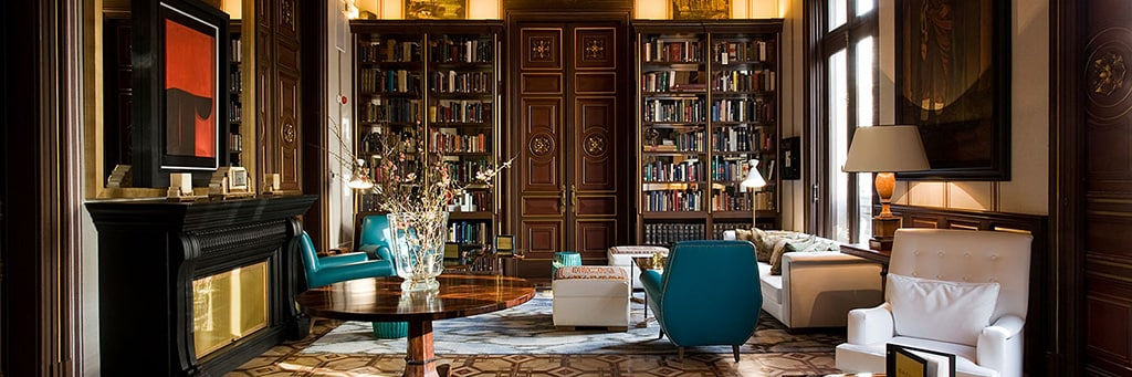 Sunlit mahogany library with elegant leather seating and floor-to-ceiling window.