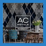 Tables and chairs in front of decorative wall, opens the AC Hotels brand page