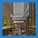 Tables and chairs in hotel courtyard, opens the Fairfield Inn & Suites brand page