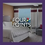 Hotel guest room with bed, opens the Four Points brand page