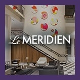 Sofas, chairs and staircase in hotel lobby, opens the Le Meridien brand page