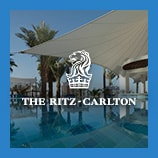 Partially canopied pool and palm trees, opens The Ritz-Carlton brand page