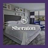 Hotel guest room with bed, opens the Sheraton brand page
