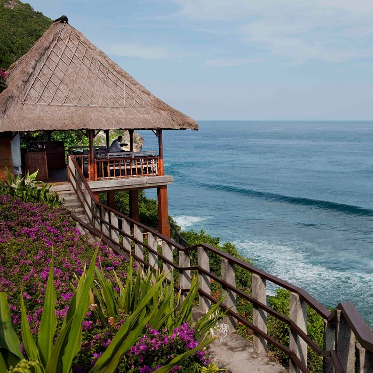 A thatched lanai and tropical gardens overlooking the surf