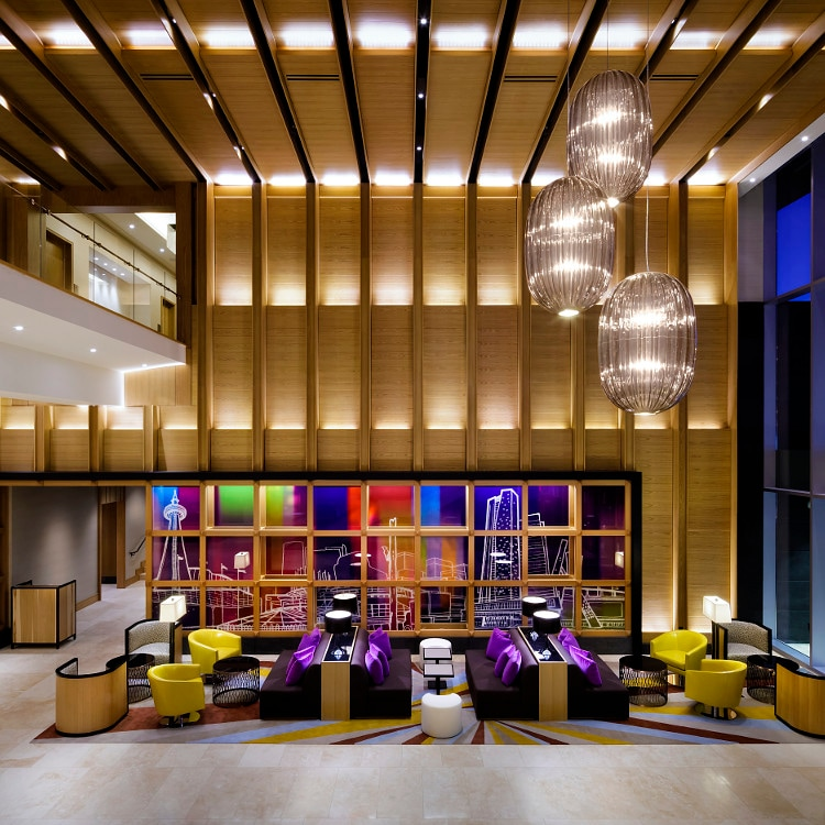 Contemporary hotel lobby with vaulted ceiling and three large seating areas