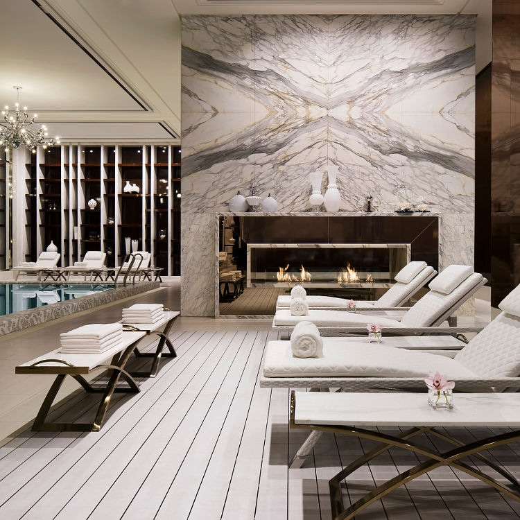 Contemporary luxury spa with poolside lounge chairs and marble fireplace