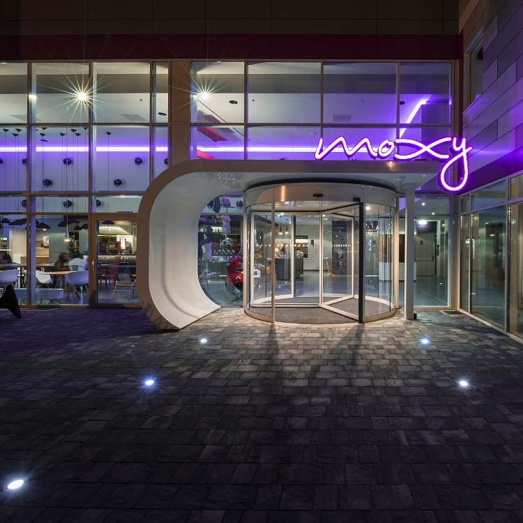 Revolving hotel front door at night with Moxy logo in neon
