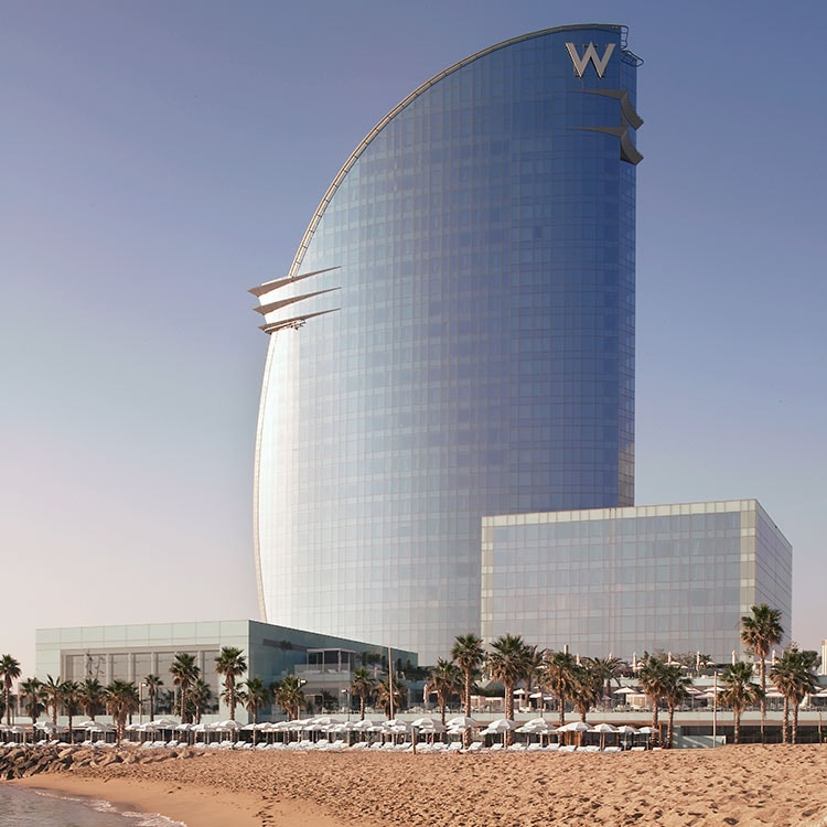 Futuristic exterior of the W Barcelona rising above palm trees and beach