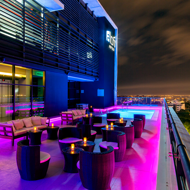 Neon-lit rooftop pool deck and lounge seating at night, with city view