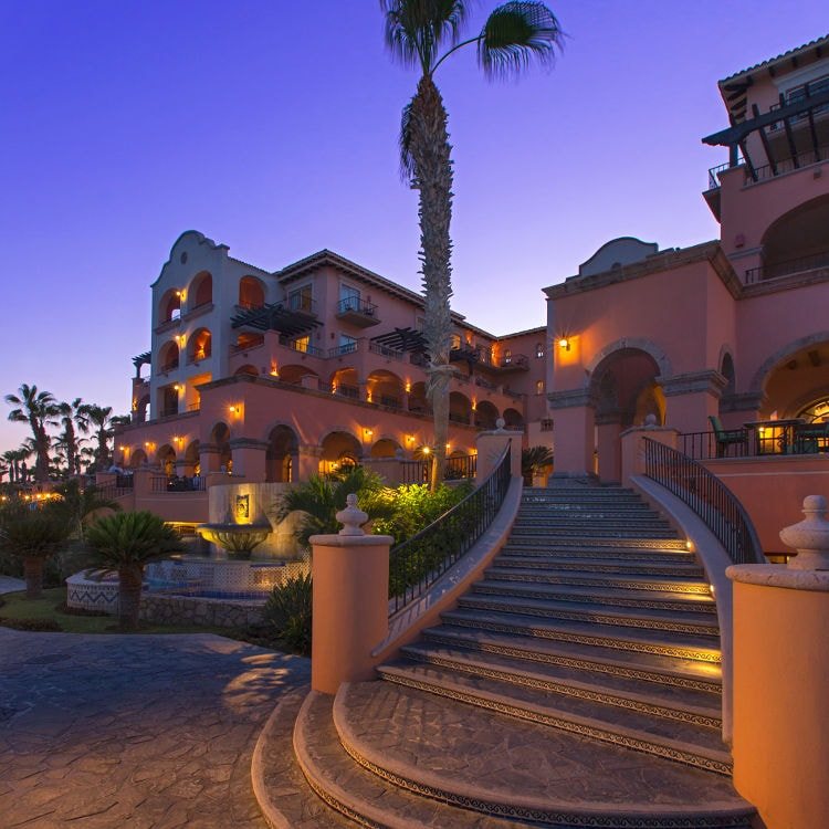 Adobe-styled hotel exterior and royal palms at night