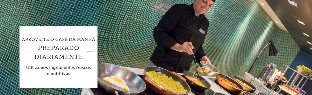 Mulher vestida de chef fazendo ovos na frigideira.