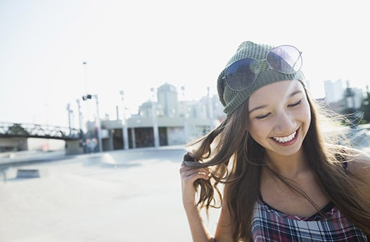 Smiling young woman wearing knit hat and tartan top