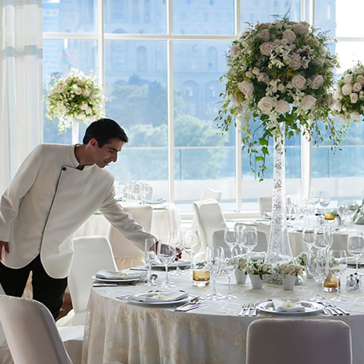 image of server setting an elegant table linked to JW Marriott Absheron Baku