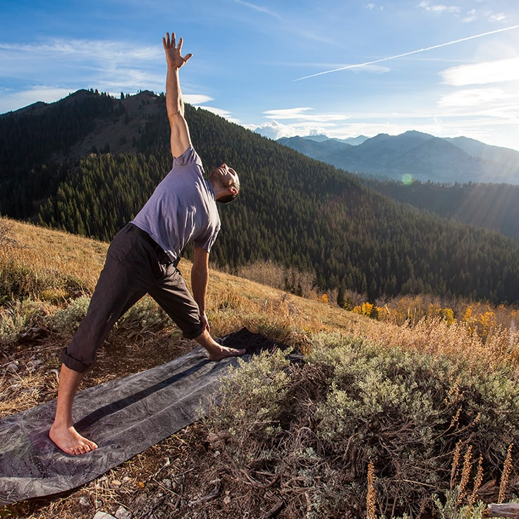 Man stretching on hill top