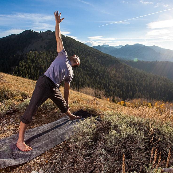 Mann macht Dehnübung auf Bergkuppe