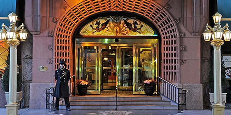 A doorman stands at the hotel entrance at night