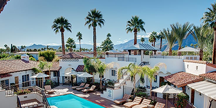 Aerial view of the hotel pool and palm trees, with San Jacinto Mountains in the background