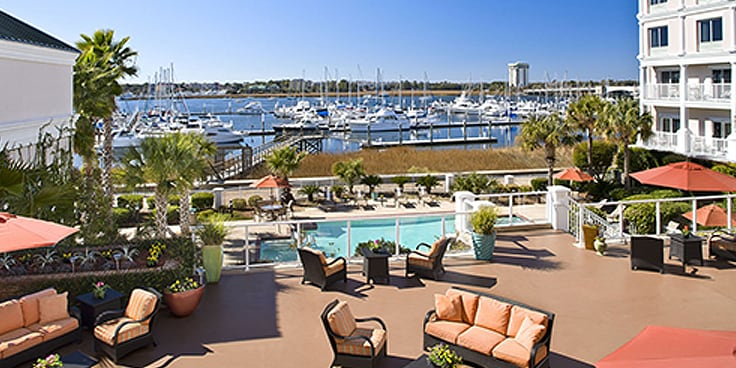 Outdoor seating area overlooking hotel pool and marina