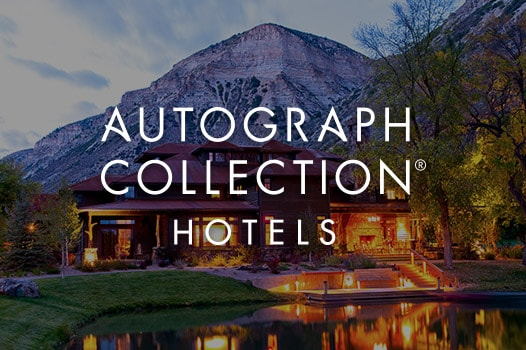 Lake and hotel façade in foreground, mountains in background and Autograph Collection logo