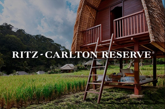 Elevated, thatch-roofed bungalow and Ritz-Carlton Reserve logo