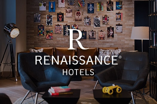 Small seating area with photo collage on the wall , Renaissance Hotels logo
