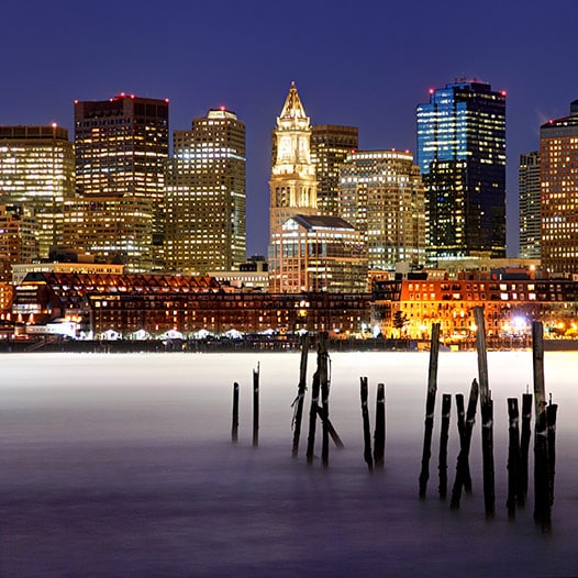 Downtown Boston skyline at night in background. Boston Harbor in foreground.