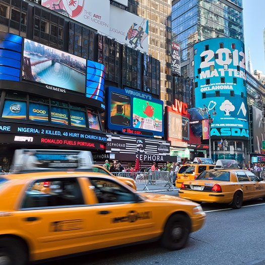 Taxis speeding past electronic billboards in Times Square.