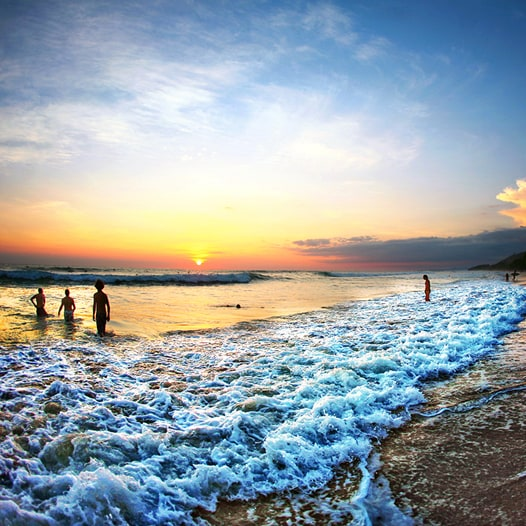 People wading into the ocean surf at sunset.