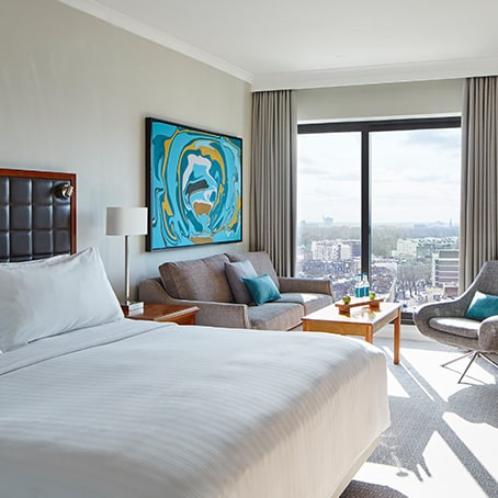 Hotel room with bed, seating area and window overlooking a city