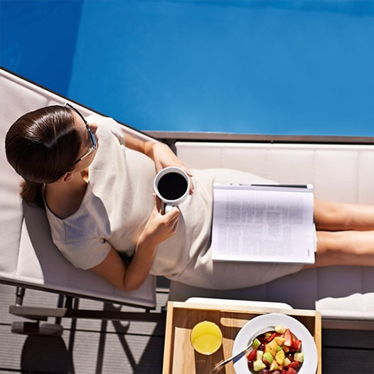 Overhead view of woman sitting near pool holding a cup of coffee