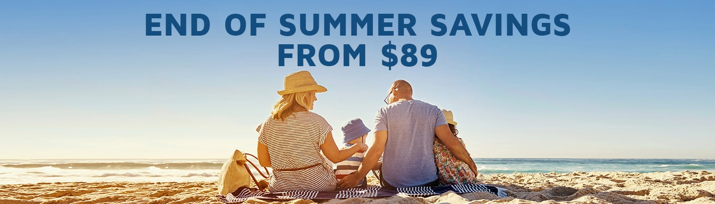 Mother, father and two small children sitting on a sandy beach | End of summer savings from $89