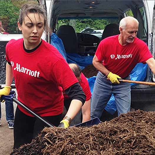 Two Marriott associates spreading mulch; Opens Our Communities page