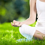 Partial view of a woman sitting on the grass in a yoga  lotus position