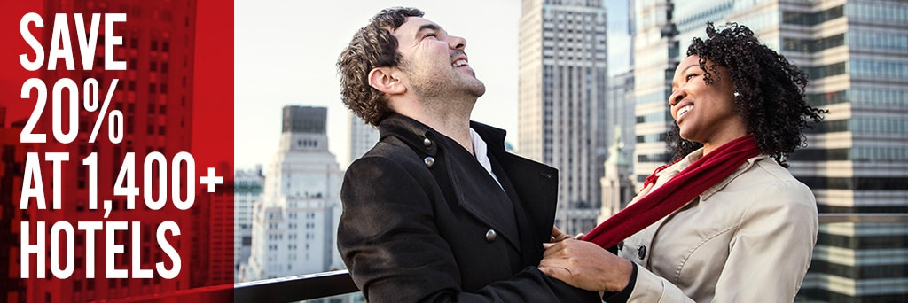 Man and woman laughing on a rooftop overlooked by tall buildings