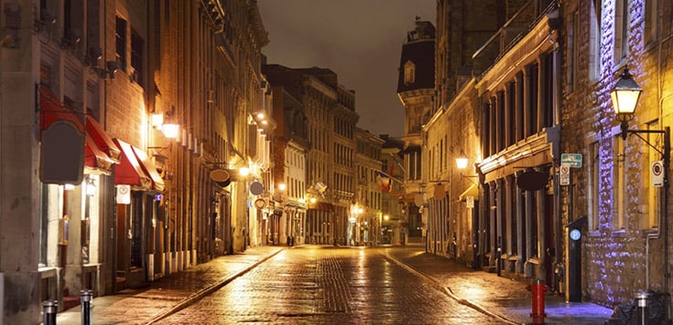 An empty pedestrian street at night overlooked by buildings