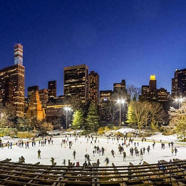 People skating on an ice rink overlooked by tall buildings
