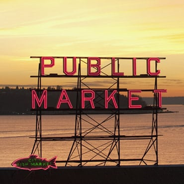 """A large sign that reads """"Public Market"""" with a view of the water behind it"""