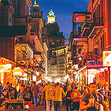 A French Quarter street bustling with people at night