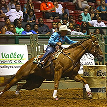 Cowboy riding horse in rodeo competition.