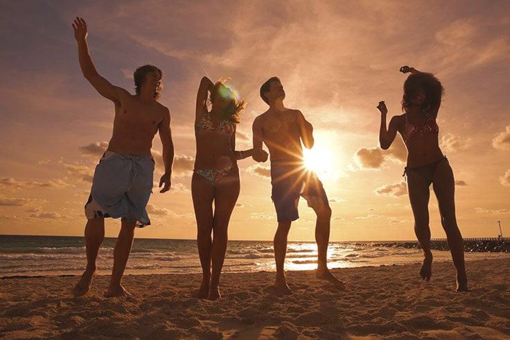 Four young people in swimsuits walking along a beach at sunset   Link to South Florida offer