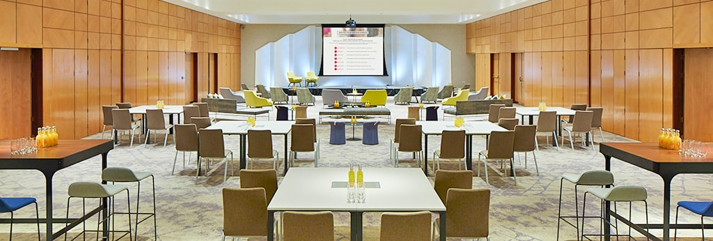 Contemporary conference room set up with tables facing a stage and monitor