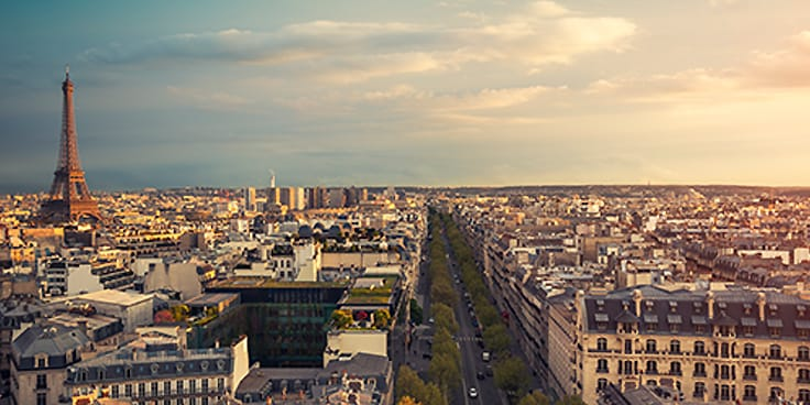 Aerial view of Paris at dusk, with the Eifel Tower in the distance