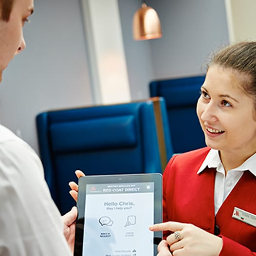 A female hotel associate shows a male guest the meeting app on a tablet