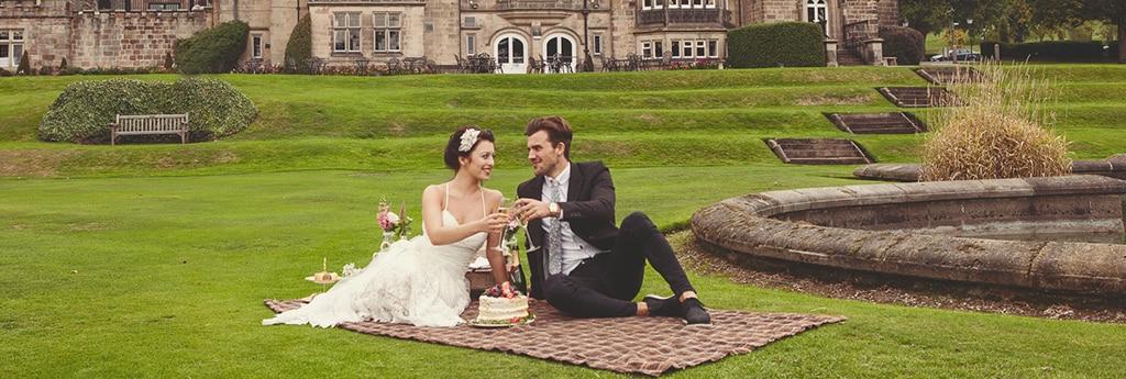 Una sposa e uno sposo su una coperta brindano con champagne e torta nuziale in hotel
