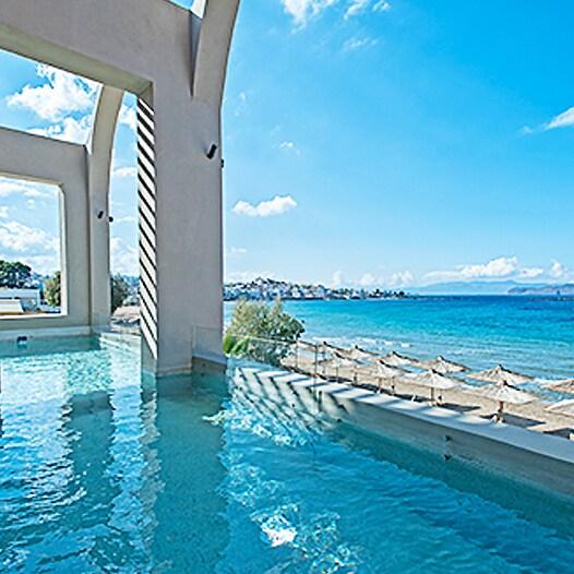 Una piscina a sfioro al coperto e i lettini che guardano verso il mare