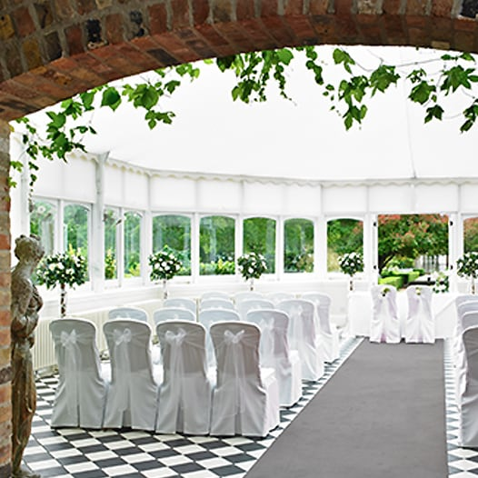 A large round tent with floral arrangements and seating for a wedding