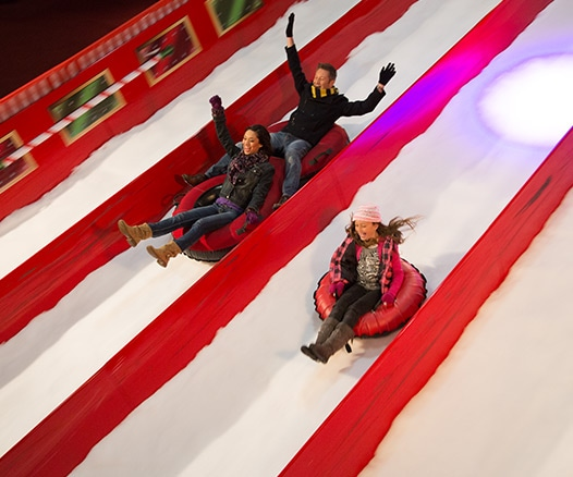 Family gliding down snow hill at Gaylord Texan's Lone Star Christmas