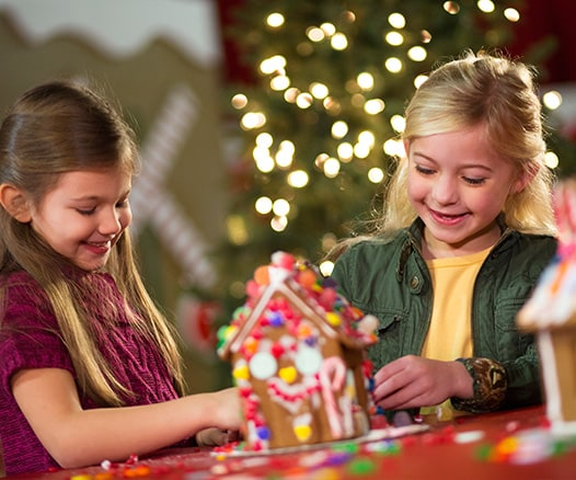 Two girls decorating a gingerbread house during Gaylord Texan's Lone Star Christmas
